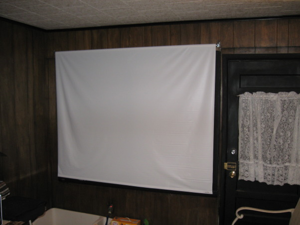 """Budget home theatre, Well, here is my home theatre! I'm not sure how to build walls, but I do know how to cut cardboard and use a staple gun. A little wrapping paper covers the ugly cardboard color and is in tune with the holiday. The projector screen is actually a pull down window shade and the futon provides the best seat in the house....., Close up of the """"screen"""". Popcorn?, Media Rooms Design"""