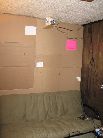 Budget home theatre, Well, here is my home theatre! I'm not sure how to build walls, but I do know how to cut cardboard and use a staple gun. A little wrapping paper covers the ugly cardboard color and is in tune with the holiday. The projector screen is actually a pull down window shade and the futon provides the best seat in the house....., This view shows the back of the theatre where seating is provided by a futon., Media Rooms Design
