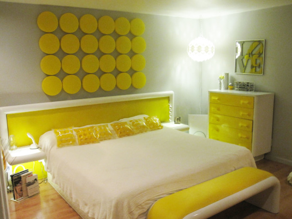 "Switched On Bedroom!, This is my master bedroom with a California King size bed and vintage headboard upholstered in yellow vinyl. The built in side tables light up! Original Eero Aarnio Brandy Glass chairs provide seating for reading. The Yellow faced dressers are made of plastic and compliment the ""Little Yellow Pills"" art work on the wall behind the bed. There is a matching dog bed, but of course!, My Switched On Bedroom in Fabulous Yellow. The walls are painted a pale grey so the white headboard would stand out better. Vintage inflatable pillows make it fun., Bedrooms Design"