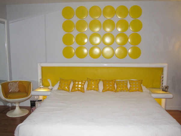"Switched On Bedroom!, This is my master bedroom with a California King size bed and vintage headboard upholstered in yellow vinyl. The built in side tables light up! Original Eero Aarnio Brandy Glass chairs provide seating for reading. The Yellow faced dressers are made of plastic and compliment the ""Little Yellow Pills"" art work on the wall behind the bed. There is a matching dog bed, but of course!, Switched On Bedroom with lots of Yellow accents; the headboard, the ""little yellow pills"" artwork and 60s inflatable pillows. The side tables light up as well. , Bedrooms Design"