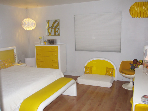 "Switched On Bedroom!, This is my master bedroom with a California King size bed and vintage headboard upholstered in yellow vinyl. The built in side tables light up! Original Eero Aarnio Brandy Glass chairs provide seating for reading. The Yellow faced dressers are made of plastic and compliment the ""Little Yellow Pills"" art work on the wall behind the bed. There is a matching dog bed, but of course!, A Robert Indiana Love mirror tops the Yellow faced highboy with matching dog bed. I am not big on window treatments. I like clean and colorful! , Bedrooms Design"