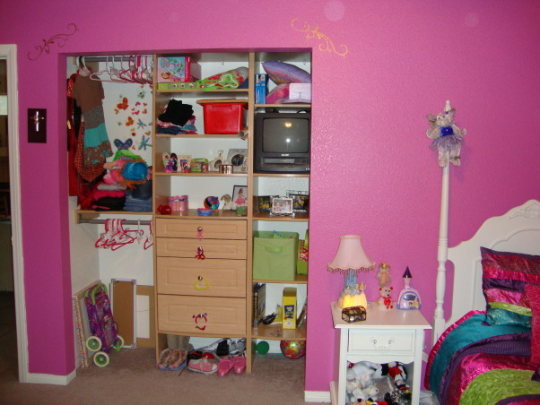 Rich Colors for an 8 year old, Girl's bedroom makeover.  Pink, turquoise, purple, and raspberry colors.  Striped comforter set and painted stripes on walls with gold stencils.  , Closet with storage.  I'm looking for something to put over the closet area, just haven't found the perfect thing just yet.  I'm thinking about a bead type curtain., Girls' Rooms Design