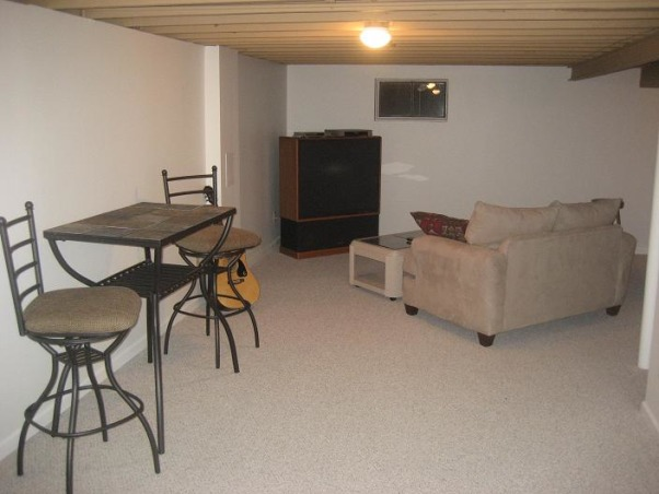 L-Shaped Basement design?, First, I'm a single guy, moved into my house a year ago, and have no eye for design.  At the moment, my basement has leftover furniture that couldn't fit in my living room, and little extras I found before moving in.  I'd like to make it into a movie room and have a bar.  There is a long stretch that I'm not sure what to do with.  I plan on finishing the ceiling once all the wiring is in place.  HELP! :), After some furniture.  This couch came with the one in my living room, but didn't have space, so I just placed it down here.  Thinking about getting a sectional and placing it where the big screen is.   , Basements Design