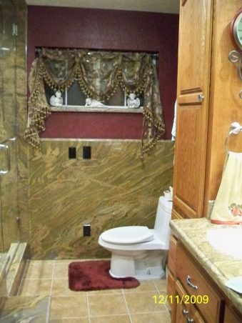 Elegant Maroon bathroom, Grantie on walls & shower. Rain shower head in the ceiling with cam lights on each side, hand held shower on wall. Nitch for shampoo and soap. Glass Shower door and wall. floor of shower is brown jade tile. Jetted tub with nitch in the wall. Tile floor. , Granite walls & dual flush toilet   , Bathrooms Design