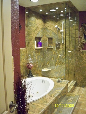 Elegant Maroon bathroom, Grantie on walls & shower. Rain shower head in the ceiling with cam lights on each side, hand held shower on wall. Nitch for shampoo and soap. Glass Shower door and wall. floor of shower is brown jade tile. Jetted tub with nitch in the wall. Tile floor. , shower nitches   , Bathrooms Design