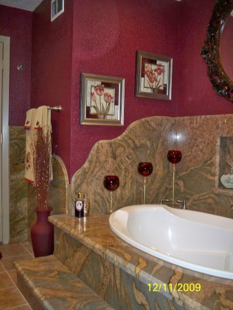 Elegant Maroon bathroom, Grantie on walls & shower. Rain shower head in the ceiling with cam lights on each side, hand held shower on wall. Nitch for shampoo and soap. Glass Shower door and wall. floor of shower is brown jade tile. Jetted tub with nitch in the wall. Tile floor. , detailed curb on wall of jetted tub   , Bathrooms Design