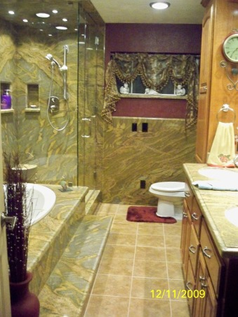 Elegant Maroon bathroom, Grantie on walls & shower. Rain shower head in the ceiling with cam lights on each side, hand held shower on wall. Nitch for shampoo and soap. Glass Shower door and wall. floor of shower is brown jade tile. Jetted tub with nitch in the wall. Tile floor. , Granite walls and counter tops  , Bathrooms Design