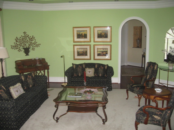 "Octagonal Living Room, This is my octagonal living room that I finally pulled together after two years in our house.  Furniture placement was a challenge due to many arch openings leading to other rooms and the entry stairs. I had the black upholsterd furniture from the start, but changed the wall color from yellow initially, to a ""potpourri"" green that harmonizes much better with the furniture.  There are touches of tangerine in the pictures, corners of the carpet, and a large vase which picks up the wall color in the adjoining family room., View from butler's pantry, Living Rooms Design"