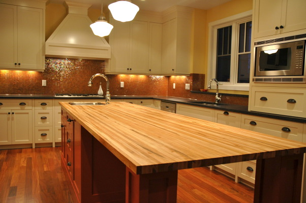 Burst of color..., This is a kitchen that was in a custom home we completed. The clients were a lot of fun and wanted that to show through with the finishing, including the orange island! Hope you enjoy the images. :) Check out my other spaces and come see my blog... http://verandainteriors.blogspot.com/, Fun clients and a fun kitchen! Cream lacquered cabinets with a burst of color and an orange lacquered island. Honed Antique Brown granite was used for the kitchen and a maple butcher block for the island. Finished off with pale yellow walls and orange glass mosaic tiles for the backs splash.  , Kitchens Design