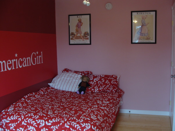 American Girl Room, My daughter wanted an American Girl Room but can't buy that at a store.  We color matched the paint at Lowes(took in a doll box) Ordered the custom sticker online. Bedding is from Target, posters were bought on Ebay because they are vintage and they don't make them anymore.Had to buy them at different times.  Daisy picture was painted by a local artist. Dressers were painted white. The flooring is bamboo. My husband was awesome through all of this.  I couldn't have done it without him!!! , American Girl posters bought on Ebay.  We also painted two of the walls pint to break up the red. , Girls' Rooms Design