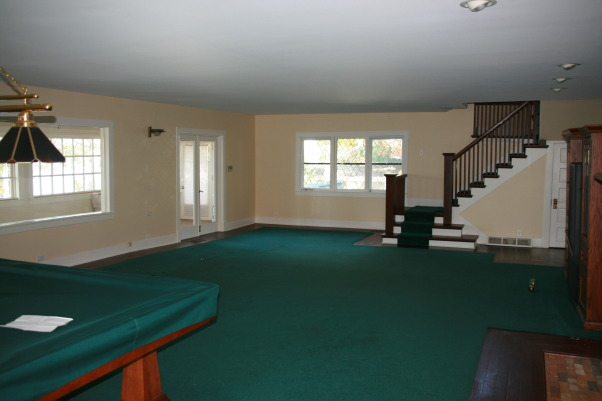 Living Room Renovation, This project was a complete home renovation.  This living room was outdated with green carpet and small sliding doors that led to a sun porch which made the space feel very dark.  We added a wall of doors to the sun porch which brought in natural light.  We also added a hallway with built-ins and a powder room that leads to the kitchen.  This really enhanced the traffic pattern throughout the first floor.  The stair case was also completely rebuilt., BEFORE photo shows a large empty space which had little natural light., Living Spaces