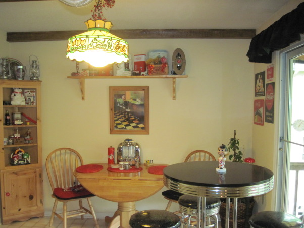 Coca Cola kitchen, Kitchen/dining room with coca cola memorabilia collected from family and friends. Trying to stay with informal diner style., Dining room with diner style sitting, vintage coca cola light, shelf with collectibles , Kitchens Design
