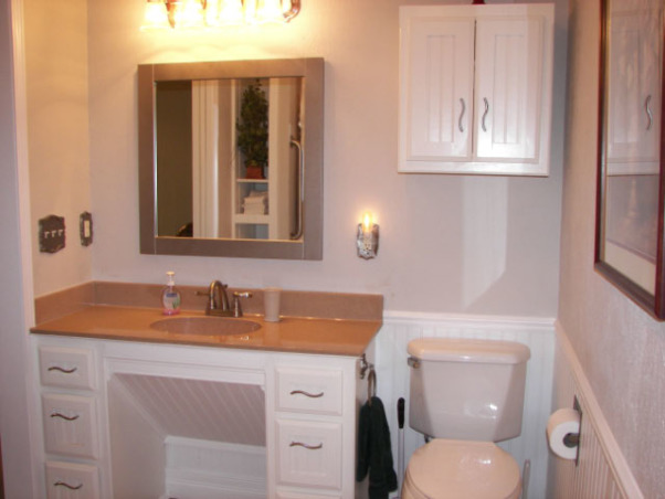 Wheelchair Friendly Bathroom, Our tiny bathroom was so small that my husband could not get his wheelchair to even go through the doorway so we added 2 feet from the bedroom and rearranged the room. We chaged the small hinged door to a pocket door.  We tiled the floor on the diagonal and put down slip resistant tile in the shower stall. We also installed appropriate handrails and a handicap toilet. Now he can wheel circles in the center of the floor and proceed right into the shower.  Although the area is still small, there is room for him to manouver and enjoy his shower!, We had the bathroom cabinet custom made to fit the width of the wheelchair under the sink with small drawers for accessibility., Bathrooms Design