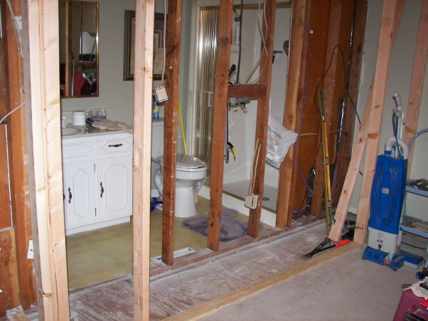 Wheelchair Friendly Bathroom, Our tiny bathroom was so small that my husband could not get his wheelchair to even go through the doorway so we added 2 feet from the bedroom and rearranged the room. We chaged the small hinged door to a pocket door.  We tiled the floor on the diagonal and put down slip resistant tile in the shower stall. We also installed appropriate handrails and a handicap toilet. Now he can wheel circles in the center of the floor and proceed right into the shower.  Although the area is still small, there is room for him to manouver and enjoy his shower!, Renovation time... we are adding 2 feet to the old bathroom., Bathrooms Design