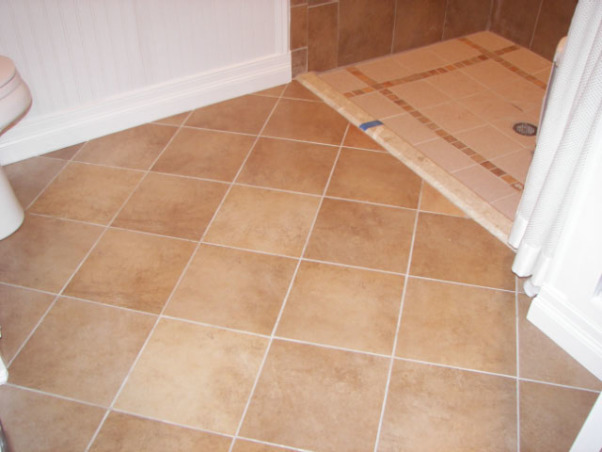 Wheelchair Friendly Bathroom, Our tiny bathroom was so small that my husband could not get his wheelchair to even go through the doorway so we added 2 feet from the bedroom and rearranged the room. We chaged the small hinged door to a pocket door.  We tiled the floor on the diagonal and put down slip resistant tile in the shower stall. We also installed appropriate handrails and a handicap toilet. Now he can wheel circles in the center of the floor and proceed right into the shower.  Although the area is still small, there is room for him to manouver and enjoy his shower!, Our tiled floor is on the diagonal to make it apprea larger - needed all the help it could get!, Bathrooms Design