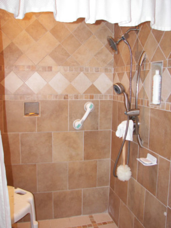 Wheelchair Friendly Bathroom, Our tiny bathroom was so small that my husband could not get his wheelchair to even go through the doorway so we added 2 feet from the bedroom and rearranged the room. We chaged the small hinged door to a pocket door.  We tiled the floor on the diagonal and put down slip resistant tile in the shower stall. We also installed appropriate handrails and a handicap toilet. Now he can wheel circles in the center of the floor and proceed right into the shower.  Although the area is still small, there is room for him to manouver and enjoy his shower!, Here is the shower with the 2 heads - one is permanent while the other one is movable for my husband who is disabled.  Not seen in the handrail at the edge of the shower., Bathrooms Design