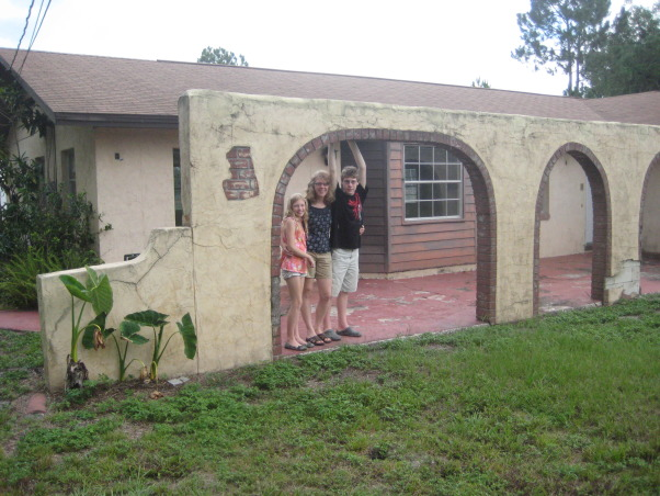 "Spanish style ranch, This is the house we just purchased in Florida.  It was built in 1969 and needs some ""freshening up.""  As we are new to this style house, I need suggestions as how to modernize the exterior - ie paint colors, landscaping.., This decorative wall looks so out of place.  We were thinking maybe a pergola with some vines over it?  I just don't know - and I really don't like the faux exposed brick.  Can that be covered?  Also, the brown wood siding looks so out of place.  Should we paint that to match the rest of the house?  What color should the house be?    , Home Exterior Design"