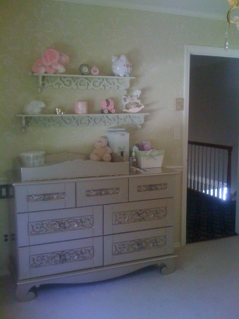Tranquil Surroundings, A baby girls' nursey. Sage green wallpaper with scroll work. Matching scrolls on antique gold wrought iron crib and book shelves.  Pink accents throughout.  Notice the scroll work on the silver dresser .  Silver and Gold metallics appear as an accent piece throughout room and play up on sparkle of chandelier.  A little girls' heaven!, Nurseries Design