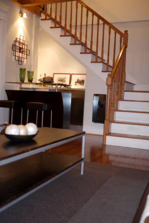 A modern and chic living room, Welcome to our living room. Come on in, have a sit and let me tell you a little bit about this room. Our space was designed to work well with our style as well as our lifestyle. We like it simple, no clutter. We like it modern looking, fresh and chic. We chose muted colors that work well together. The wooden beams and fireplace are the focal point of the room. It is the first thing people talk about when they come in the house. My brother-in-law did the two beautiful paintings that flank the fireplace. He actually painted them after the room was done. And we think he did a beautiful job. When we hung the paintings on the wall, it was like putting the perfect, well matched icing, on the cake. We are very pleased with how everything turned out. What about you?  What do you think? Feel free to e-mail me at patchi@trendypeas.com for all the sources., Bar area and stairs , Living Rooms Design
