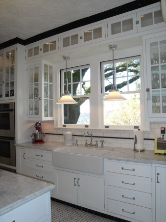Authentic 1927 Kitchen Vintage Remodel - White White White and Black, I have always had a strong desire to create and restore since I was a little girl.  My husband and I have been restoring a historic bed and breakfast for the last 3 years and we are almost ready to open.  One of the last rooms (and most important) that we restored is our 1927 kitchen.  As a graphic designer, I designed my kitchen on computer first and it turned out exactly as planned!  Details are everything!  We wanted to keep it authentic and hide as much modern as possible, but still make it functional for today's day and age.  Everything has hydraulic pullouts, including the decorative hood around the oven.  We also used subway tile, pressed tin ceiling, basketweave marble, and a lot of glass.  This has been a labor of love...hope you enjoy the pictures!  :), The cabinets are custom made and painted in the true style of the twenties...some high and out of reach.  The last detail of this kitchen (which is not pictured) is a library ladder and a chrome rail that can access these easily.  The drawers on the right are a false door that conceals a modern dishwasher.         , Kitchens  Design