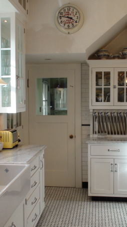 Authentic 1927 Kitchen Vintage Remodel - White White White and Black, I have always had a strong desire to create and restore since I was a little girl.  My husband and I have been restoring a historic bed and breakfast for the last 3 years and we are almost ready to open.  One of the last rooms (and most important) that we restored is our 1927 kitchen.  As a graphic designer, I designed my kitchen on computer first and it turned out exactly as planned!  Details are everything!  We wanted to keep it authentic and hide as much modern as possible, but still make it functional for today's day and age.  Everything has hydraulic pullouts, including the decorative hood around the oven.  We also used subway tile, pressed tin ceiling, basketweave marble, and a lot of glass.  This has been a labor of love...hope you enjoy the pictures!  :), This is a little premature...just finishing the paint behind the clock...an original advertisement clock from the late 30's that looked nice in this spot (hard wired).      , Kitchens  Design