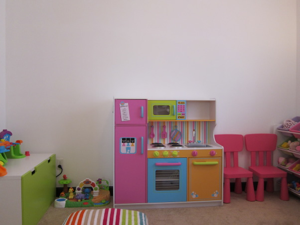 Playroom for 2 year old - Additional Pictures!, Instead of having toys all over the family room, we converted our spare bedroom into a playroom for our 2 year old daughter.  I didn't want to paint again, so I left the white walls and the black trim which I don't think is that noticeable - and besides, it matches the TV.  I am still not finished, but have tried to decorate the room around the colors in the kitchen.  I am thinking about putting one of those cables on the wall with the kitchen to hang her artwork.  Please let me know what you think., The wall with the kitchen, which was my inspiration for the colors in the room.       , Girls' Rooms Design