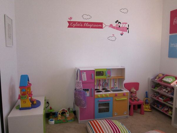 Playroom for 2 year old - Additional Pictures!, Instead of having toys all over the family room, we converted our spare bedroom into a playroom for our 2 year old daughter.  I didn't want to paint again, so I left the white walls and the black trim which I don't think is that noticeable - and besides, it matches the TV.  I am still not finished, but have tried to decorate the room around the colors in the kitchen.  I am thinking about putting one of those cables on the wall with the kitchen to hang her artwork.  Please let me know what you think., New decal added to the wall - view when the door is opened.    , Girls' Rooms Design