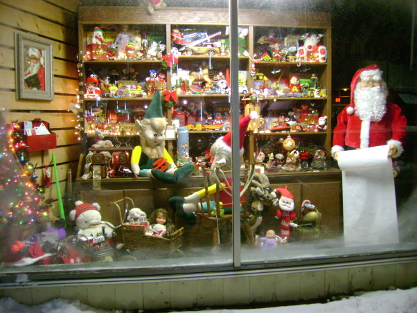 "Christmas Store Front Windows, This year I placed my Santa Workshop in the windows of a local florist in our little downtown area. I purchased a full size Santa to add to the space as well as a bucket of coal. You can see the original display in my other post, ""Santa rents a room at my B&B"", Last year we were on the Tour of Homes. When friends of ours saw our sewing room display, they wanted it for their windows of their florist shop this year.  , Holidays Design"