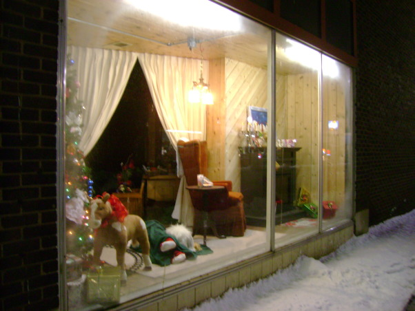 "Christmas Store Front Windows, This year I placed my Santa Workshop in the windows of a local florist in our little downtown area. I purchased a full size Santa to add to the space as well as a bucket of coal. You can see the original display in my other post, ""Santa rents a room at my B&B"", The long view of the Living Room window  , Holidays Design"