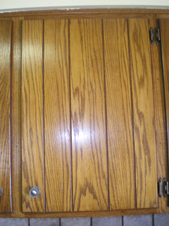"Barn door kitchen cabinets, Our kitchen deserves a -3 rating right not, but we are remodeling our house room by room, and have saved the kitchen for last.  The kitchen is not huge, but decent-sized, with fairly good configuration.  But we HATE these cabinets with their barn door look, deep vertical grooves, and overwhelming amount of oak.  My husband absolutely refuses to consider replacing the cabinets due to cost, and also the fact that he feels the cabinets themselves are perfectly good.  He wants to plane the cabinet doors to get rid of the grooves, and then paint or stain.  I'm not convinced this will work.  For one thing, the doors seem quite thin already.  I'm all for re-using what we can, but would love some suggestions for remaking the doors and adding some ""furniture-like"" details.  Please help!, Close-up of kitchen door in desparate need of update.  Grooves are about 4-1/2 inches apart on every single door and drawer front.  Hubby wants to plane fronts to get rid of the grooves.  I am leaning toward adding moulding to the perimeter, and then of course painting or staining darker.  , Kitchens Design"