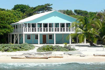 Utila Beach House with Long Living Room, I am enclosing a front porch to make a long living room (12'x 36'). I'm having problems figuring out what furniture to get and how to place it. There are three double doors opening onto the new front porch with a view of the ocean, which I want to take advantage of. Any suggestions would be greatly appreciated!, EDIT: The addition is now complete! This is one of the old photos. I want to leave the comments, so will not delete this photo yet...     This is the front of the house now. The new porch will have a metal hip roof that breaks up the large area of aqua. The porch rail has white rope lines below the cap instead of boards for a cleaner look, and the number of posts/sections will be reduced for a less cluttered look. I will post new photos after the construction is complete - hopefully by the end of May or early June.       , Living Rooms Design