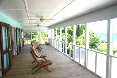 Utila Beach House with Long Living Room, I am enclosing a front porch to make a long living room (12'x 36'). I'm having problems figuring out what furniture to get and how to place it. There are three double doors opening onto the new front porch with a view of the ocean, which I want to take advantage of. Any suggestions would be greatly appreciated!, EDIT: The addition is now complete! This is one of the old photos....     This is a view of the 12 x 36 porch that is going to be enclosed to create a new living room. There will be a new porch added to the front of the house. It will be the same size, but the ceiling will be painted wood over beams under a hip roof - not flat like this one.   The beachfront view is stunning, so we spend a lot of time on the porch. Opening the double doors will make the porch an extension of the living room. The 12' roof overhang keeps the sun out of the living area, plus makes it possible to leave the doors open during rain storms. I made cushions for the porch chairs, but they were not done when this photo was taken.         , Living Rooms Design