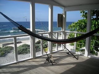 Utila Beach House with Long Living Room, I am enclosing a front porch to make a long living room (12'x 36'). I'm having problems figuring out what furniture to get and how to place it. There are three double doors opening onto the new front porch with a view of the ocean, which I want to take advantage of. Any suggestions would be greatly appreciated!, EDIT: The addition is now complete! This is one of the old photos. I want to leave the comments, so will not delete this photo yet....     Hammocks are hung in both corners of the front porch. That is an almond tree on the right side of the photo. The dock can be seen in the background. One detail that I really like is that we bordered the plants in the yard with coral rock standing on end like a picket fence, instead of the usual low stacked wall that is common on the island.     , Living Rooms Design