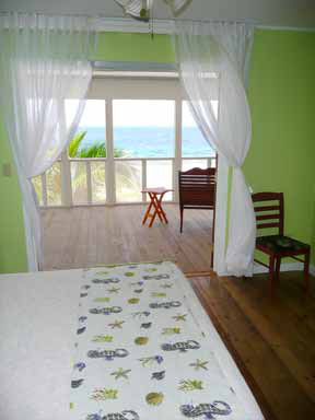 Utila Beach House with Long Living Room, I am enclosing a front porch to make a long living room (12'x 36'). I'm having problems figuring out what furniture to get and how to place it. There are three double doors opening onto the new front porch with a view of the ocean, which I want to take advantage of. Any suggestions would be greatly appreciated!, EDIT: The addition is now complete! This is one of the old photos. I want to leave the comments, so will not delete this photo yet....     This photo shows the door that will become the bedroom closet. It will be about 5' or 6' wide and extend into the new living room about 2' deep.   I made a bed scarf for the foot of the bed with seahorses-and-shells fabric. I'm trying to get an island decor that is understated. Well, okay the COLOR is not understated! LOL But the feel of the house is very comfortable. The bed has a natural cotton spread, which matches the curtains on the windows.   All the moldings are a simple contour that is painted gloss white throughout the house. The construction crew used a router to make every piece by hand.         , Living Rooms Design