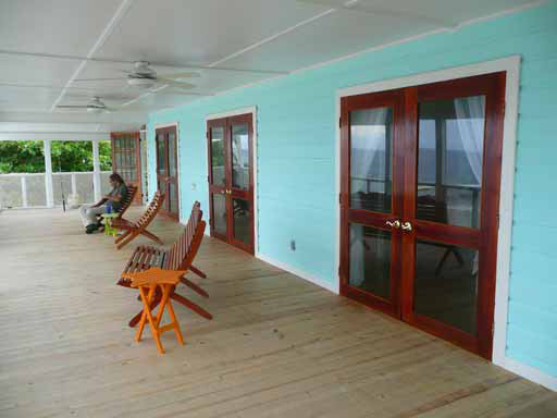 Utila Beach House with Long Living Room, I am enclosing a front porch to make a long living room (12'x 36'). I'm having problems figuring out what furniture to get and how to place it. There are three double doors opening onto the new front porch with a view of the ocean, which I want to take advantage of. Any suggestions would be greatly appreciated!, EDIT: The addition is now complete! This is one of the old photos....     The doors are native Honduran wood, similar to Mahogany, and were made on the island of Utila. They open flat against the wall. We have a hook for the operating door handle and a small bolt at the bottom of the door with the decorative non-working handle to hold them open.   The door at the far end is a screen door that is at the top of the stairs. The first and third double doors go into the bedrooms, and the center door opens into the dining room/kitchen.   When all of the doors and windows are open, the breeze goes through the house and makes it very comfortable. In fact, on one windy day, the blankets and pillows were blown off the beds!  The aqua exterior siding will be duplicated on the new porch, but it will be removed in the new living room and wall board will be used for a smoother surface.         , Living Rooms Design