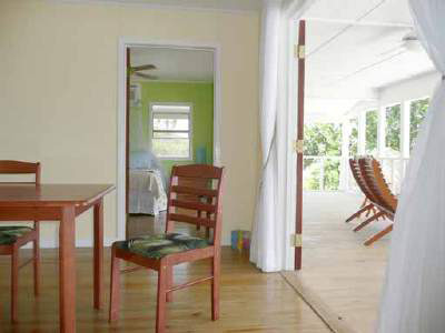 Utila Beach House with Long Living Room, I am enclosing a front porch to make a long living room (12'x 36'). I'm having problems figuring out what furniture to get and how to place it. There are three double doors opening onto the new front porch with a view of the ocean, which I want to take advantage of. Any suggestions would be greatly appreciated!, EDIT: The addition is now complete! This is one of the old photos. I want to leave the comments, so will not delete this photo yet....     This shows the yellow walls in the dining area. This color will be used in the new living room to unite them visually. The door opening will not have the sheer curtains as shown here.   The small door goes into the green bedroom - the other side of the dining area has a door going into the blue bedroom that is exactly the same.   I covered the seats on the dining chairs with a palm print fabric. As you can see, I prefer simple furnishings for a cleaner look.         , Living Rooms Design