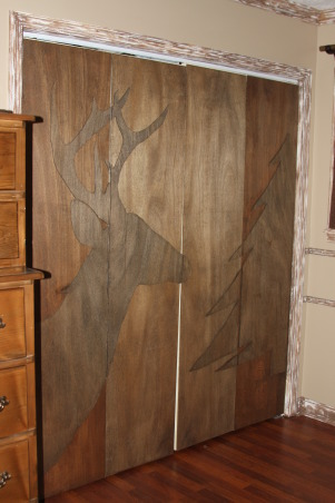 "A Hunter's Haven, I designed a ""hunter's haven"" for by 14 year old son's bedroom.  We are very outdoors-y and he loves to hunt. I used lots of Mossy Oak Break Up Pattern camo fabric and original designs using wood and other materials., This his closet.  I covered the folding doors with wood panelling stained with walnut stain.  I cut out the dear head and tree with jigsaw and placed the pieces on each door. When closed, it's a cool art work accent to his room.      , Boys' Rooms Design"