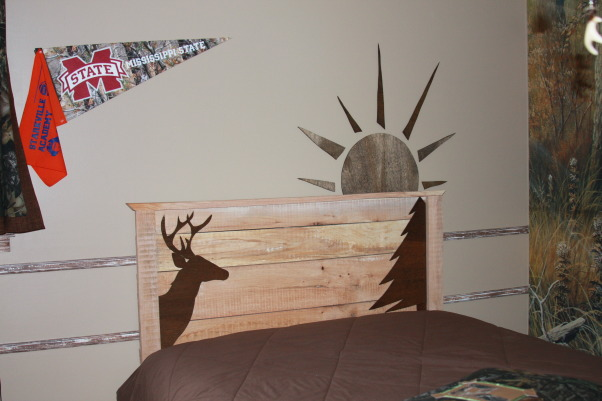 "A Hunter's Haven, I designed a ""hunter's haven"" for by 14 year old son's bedroom.  We are very outdoors-y and he loves to hunt. I used lots of Mossy Oak Break Up Pattern camo fabric and original designs using wood and other materials., My son's ""2nd dad,"" Bill, built this headboard from a tree that was uprooted during Katrina. I cut the deer and tree with my jig saw out of wood panelling. The sunrise is on the wall. I made it with my jigsaw as well.      , Boys' Rooms Design"