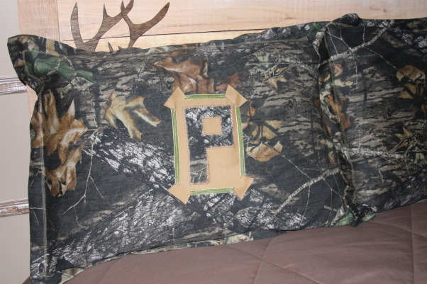 "A Hunter's Haven, I designed a ""hunter's haven"" for by 14 year old son's bedroom.  We are very outdoors-y and he loves to hunt. I used lots of Mossy Oak Break Up Pattern camo fabric and original designs using wood and other materials., Pillow shams for bed with his sir name initial on them.      , Boys' Rooms Design"