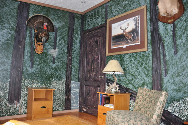 Man Cave/Spare Room, Hunting Man cave that serves as a spare room from time to time., These two walls show the painting of the woods and the finish on the doors to look like tree bark.  I used a crackle finish to get the look of the bark on the doors and trees.  I covered a chair that I purchased at a sale for $5.00 with a camo like blackout drape I found in a clearance sale. , Bedrooms Design