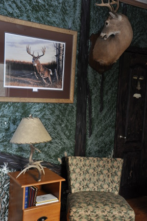 Man Cave/Spare Room, Hunting Man cave that serves as a spare room from time to time., The deer mount is called a grooming mount and the print on the wall is from a canadian artist.  The lamp was purchased at one of the Rocky Mountain Elk Foundation banquets.  The chair is an auction find and the cover is a black out drape from a sale bin. , Bedrooms Design