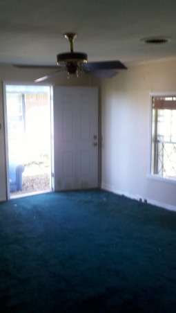 Clean and Buyer Friendly: Second Living Area, This room used to be a garage a few decades ago, and was never correctly renovated - the walls and carpet padding were completely rotted and covered in mold, the forest green carpet smelled like years of animals, there were outlets and holes covered by cheap wood paneling and nothing about that room was built with a level. We wanted to make it a safe, buyer friendly and  presentable space as inexpensively as possible. We still need to finish the paint and install the new ceiling fan and crown molding., BEFORE: This room used to be a garage a few decades ago, and was never correctly renovated - the walls and carpet padding were completely rotted and covered in mold, the forest green carpet smelled like years of animals and mold. Our first decision was to paint over the old wood paneling and sell it as it - but when we tried to nail the wood paneling that was coming up off the wall back down we realized there was no drywall, insulation or anything but the frame of the wall behind it to nail it to. So we made the decision to take all the paneling off, put real walls up where there were none, remove the ceiling sound tiles, and texture and smooth everything out. So glad we made that decision because the mold we found was under the paneling was disgusting! And we found a bonus hidden outlet that was covered up with paneling on this wall. We still need to paint the room again and install the new ceiling fan and crown molding. Also, I'm thinking about installing a new side door with a big window in here to allow more light it. The only window in this room faces east so it can be very dark most of the day. I would want to frost the glass on the door as an easy, inexpensive was to provide privacy from the sidewalk. Thoughts?   , Living Rooms Design