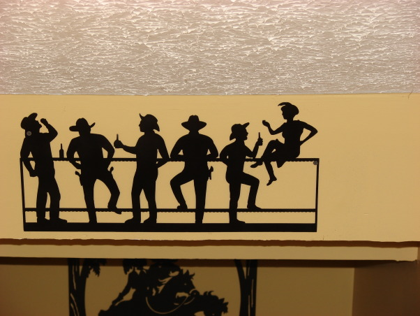 Western Saloon, Basement bedroom converted into a fancy Western Saloon with a Dining area., Coming down the stairs there is an overhang, this is a plasma cut silhouette of a bar scene with the dancing girl sitting on the bar and the cowboys standing at the bar., Other Spaces Design