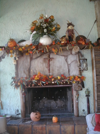 Mantel decor of pumpkin,okra, found objects., My Fall decorating  mantel decor is a seasonal affair. I love the fall colors of orange, red,yellow,brown.The warmth from these fall colors inspire me to  think of other fall items.In 2009 A stray arrow,copper plates, hand made spider webs,scarecrow,reclaimed fishing corks,dried okra pods from my garden,a goose,a golden collection of fall flowers placed in a cream colored vase on top of the mantel, an old lantern, and a cross,  Then in 2010 I painted my mantel a sea blue and added a sea horse placed on top of my mantel, bottles of red,green, blue and purple,hand made pumpkins from ole worn out pillows,and a different cross from my collection of Reclaimed Objects to bring my fall decor to read from the cold of the sea to the warmth of fall. In 2011: I added goose feathers to my fall collection moved another different cross,from my collection of Reclaimed Objects to the center of the mantel added a fire screen with a golden moon.Moved the fall flowers into a wire dove basket and placed it in front of the fire screen.The basket of fall flowers will be moved somewhere else once I start my first fire of the year.  , Other Spaces Design