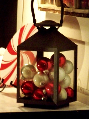 Sweet Christmas 2011, My outdoor Christmas decorating this year took a sweet turn.  Inspired by candy canes, peppermints and lollipops, I couldn't be happier with the results.  A lot of the decorations were handmade and handpainted.  I hope you enjoy!!  Merry Christmas , A glass lantern filled with red and white ornaments sit on the old black writing desk on the front porch of the house. , Holidays Design