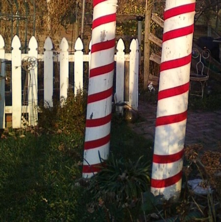 Sweet Christmas 2011, My outdoor Christmas decorating this year took a sweet turn.  Inspired by candy canes, peppermints and lollipops, I couldn't be happier with the results.  A lot of the decorations were handmade and handpainted.  I hope you enjoy!!  Merry Christmas , In the garden, two old wodden salvaged porch pillars wrapped in red velvet ribbon looks like hugh peppermint stick. , Holidays Design