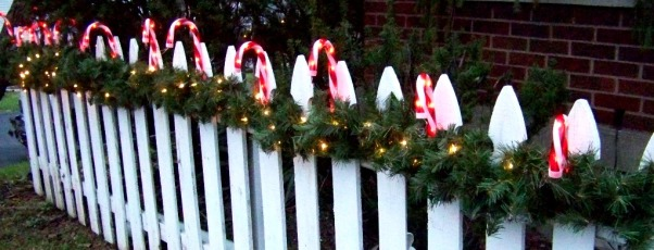 Sweet Christmas 2011, My outdoor Christmas decorating this year took a sweet turn.  Inspired by candy canes, peppermints and lollipops, I couldn't be happier with the results.  A lot of the decorations were handmade and handpainted.  I hope you enjoy!!  Merry Christmas , Greenery strung along the white picket fence serves as a base for festive candy cane lights that look so inviting when burning in the darkness. , Holidays Design