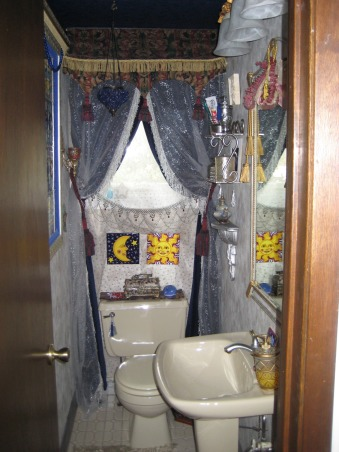 Princess Poopatorium Half bath, I shoved all my favorite things that didn't go anywhere else into this 3'x7' Italian  Renaissance Bordello a la Turkey half bath.   Main colors are silver, gold, and blues with touches deep red and deep green. Woodwork is painted silver.  Original to the room were the cream floor tiles, toilet and sink. The rest I added.  Except for the tiles artwork, the cost for the room (using an electrician and wallpaper installer) was under $1000.  The wallpaper is silver faux flat finish. The drapes on the one window is a see-through underdrape with tiny gold stars. The main drape is navy floor-length velvet with tiebacks. The drape over the velvet is see-through silver swirls with silver fringe I sewed on the edge. I made the canopy with tassels.  The top edge of the room uses detailed silver molding that I ordered from a picture frame shop and glued gold fringe to. Behind the fringe I had my electrician install rope lighting all the way around the room (but blackened out with electrical tape behind the canopy). The ceiling is wall papered in midnight blue with tiny stars.   The framed tile art is a reproduction of 15th century tiles in a Turkish museum hand made for me. The tiles over the toilet are from Italy., Given the tight space of this 3'x7' half bath, I figured hiding the fact that it was tight seemed pointless, so I reveled in it by shoving lots of stuff in there, but nothing that physically gets in the way--just visually to give you lots of look at while sitting or standing there., Bathrooms Design
