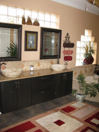 Bathroom for the birds, Beginning with a neutral backdrop of tumbled marble in earth tones coupled with old world scrolled towel racks, this room ended up being anything but neutral or  traditional.  However, it is the hot spot for everyone who comes to our house.  The peacock over the tub was custom painted for my livingroom but I did not like it in there.  So, one day while feeling adverturesome, I moved it over the tub and voila...a space was born.  The rug is wool in a contemporary pattern to keep our feet warm on cold winter mornings.  The cabinets have deep drawers to HIDE all of our grooming gear.  Best decision we ever made.  We went with chrome fixtures since they are timeless. The plants were brought in as nursery newborns and we found out quickly they thrive in the humidity.  The chandelier casts an orange glow in the room at night creating ambiance beyond your wildest dreams.  , Just to the left of the tub are his and her sinks atop a contemporary cabinet with deep drawers to hide grooming supplies but keep them handy.   , Bathrooms Design