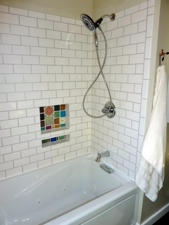 Bungalow Bath Remodel, Updated a bathroom in our brick bungalow that still had the original tile, floor and tub.  Used unusual components, our own skills and elbow grease.  This bathroom was remodeled for less than $2500 - and that is with hiring an electrician and plumber for the code work., subway tile bath surround, mosaic tile niche, Bathrooms Design